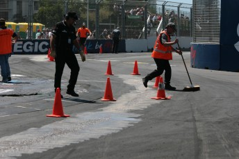 Track officials work on the turn one chicane between V8 Supercar races yesterday