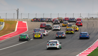 The V8 Supercars field heads through Turn 1 at the COTA
